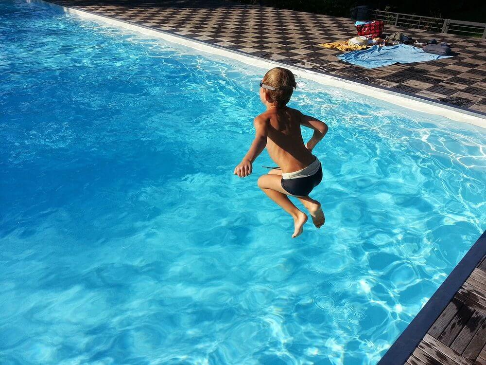 Chlapec skáče do bazénu