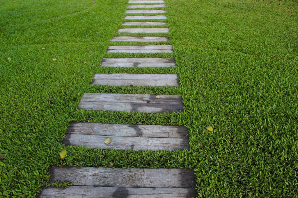 Dřevěná pěšina uprostřed trávníku